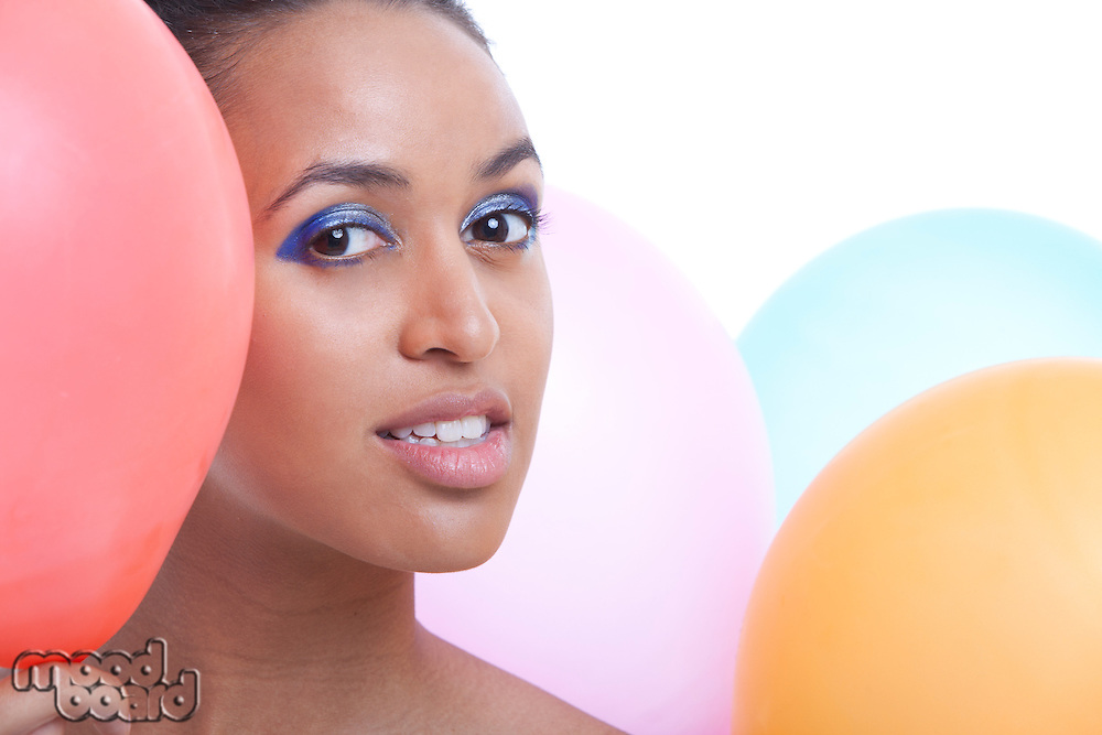 Portrait of beautiful young woman with balloons against white background