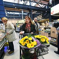 Nederland, Amsterdam , 26 november 2014.<br /> Opening Foodmarkt van Jumbo in amsterdam Noord.<br /> Op 26 november gaat de grootste Jumbo van Amsterdam open. Niet alleen de omvang van de winkel (waarschijnlijk zo&rsquo;n 2600 m2 ), ook de locatie is speciaal. De enorme foodmarkt zit in een oude loods op het voormalige Storkterrein, een van de meest creatieve plekken van Amsterdam. Hoe groot de foodmarkt precies is, hoe hij eruit gaat zien en wat er te beleven is, houden ze bij Jumbo nog geheim.Wel is duidelijk dat er vanaf woensdag in deze industri&euml;le loods zal worden gekokkereld in meerdere foodmarktkeukens &lsquo;door koks en andere vakspecialisten&rsquo;.&nbsp;En dat de producten van Jumbo gezond, lekker&nbsp;en betaalbaar zijn, aldus Jumbo.<br /> Op de foto: De eerste bezoekers van de foodmarket worden verwend met een bloemetje<br /> Foto:Jean-Pierre Jans