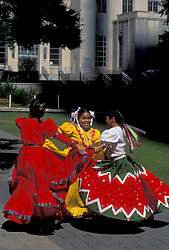 Stock photo of three young girls dancing in traditional Mexican dresses during the Cinco de Mayo celebrations in downtown Houston Texas