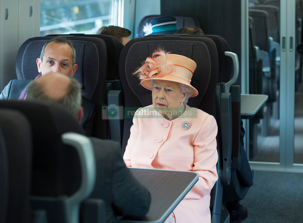 Queen Elizabeth II sits next to Isambard Thomas, Great Great Great Grandson of Isambard Kingdom Brunel, on a train travelling from Slough to Paddington Station to mark the 175th anniversary of the first train journey by a British monarch.