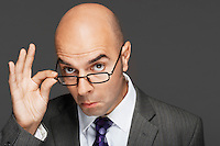 Balding man hand on glasses making a face