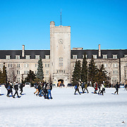 Johnston Hall in winter is rushed past by a group of cold students on their way to class.  Photo by Mido Melebari