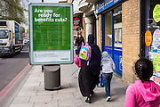 "A muslim family walk past an information poster from Hackney Council asking: ""Are you ready for benefits cuts?"" on a busy road in Stoke Newington, Hackney, London, UK."