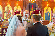 Bride and groom wearing crowns during a greek orthodox wedding