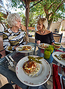 U.S.A., New Mexico. Lundeen Inn Of The Arts, Las Cruces. Linda Lundeen (l.) and her niece Terri Coffman serving Huevos rancheros.