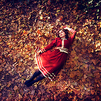 A girl lying on her back on colourful autumn leaves in a red Victoriana dress, in a dance like position, shot at bird's eye view