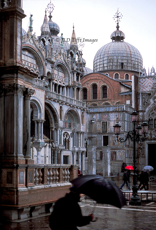 San Marco Basilica, western corner of the facade, in the rain.  Pedestrians holding umbrellas scurry past. In the foreground, a pedestrian holds a large black umbrella. Raised walkways are in place in expectation of acqua alta.  Pavement is rain-slicked.
