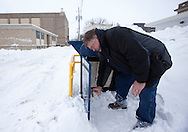 United States Postal Service employee Brian Jobes sprays the lock on a mail collection box to keep it from freezing up in Grinnell, Iowa on Wednesday February 2, 2011.