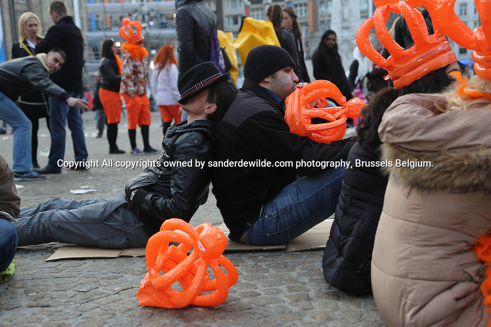 30th April 2013 Amsterdam, Netherlands. Dam Square. Queen Beatrix' abdication takes place, and her son Prince Willem-Alexander will be King of the Netherlands. A boy sleeps under his hat at the Dam square, awaiting the event.