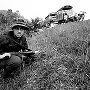 A female FARC fighter crouches in a ditch as bullets fired by Government soldiers fly overhead. The FARC were holding 40 civillians as a human shield at an illegal roadblock to provoke a response from the troops.<br />