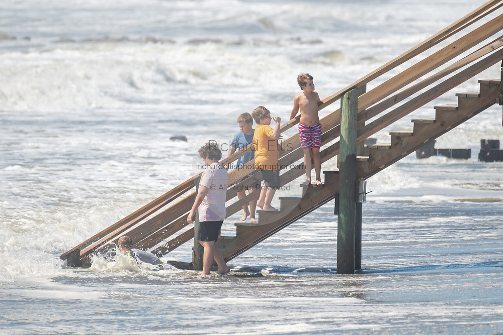 Folly Beach, South Carolina, USA. 03 September 2019. Children use the safety of deck stairs to watch the tide consume the beach as extreme tides and waves roll in ahead of Hurricane Dorian September 3, 2019 in Folly Beach, South Carolina. The slow moving monster storm devastated the Bahamas and is expected to reach Charleston as a Category 2 by Thursday morning.