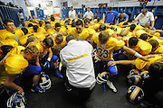 Mountain Home High School head football coach Benji Mahan prays with his team before a game.