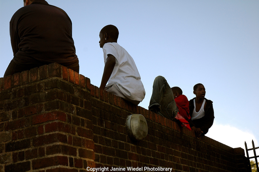Young lads out of school bored and fed up sitting on wall in Brixton South London waiting.