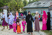 26 OCTOBER 2012 - PULASAIZ, NARATHIWAT, THAILAND:  Women and children walk into Mosque for Eid al-Adha services in the villiage Pulasaiz, in the province of Narathiwat, Thailand. Eid al-Adha, also called Feast of the Sacrifice, is an important religious holiday celebrated by Muslims worldwide to honor the willingness of the prophet Ibrahim (Abraham) to sacrifice his firstborn son Ishmael as an act of submission to God, and his son's acceptance of the sacrifice before God intervened to provide Abraham with a ram to sacrifice instead. In 2012 Eid al-Adha was celebrated Oct 25 - 26.    PHOTO BY JACK KURTZ