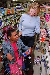 Care manager helping young woman with Cerebral Palsy in supermarket,