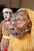 A performer and a masked 'shisa' or lion god perform for a crowd of tourists at the Ryukyu Mura theme park on the main island of Okinawa, Japan.