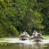 Two skiffs motor along Pahuachiro Caño after a morning wildlife watching excursion. Pacaya Samiria National Reserve, Upper Amazon, Peru.