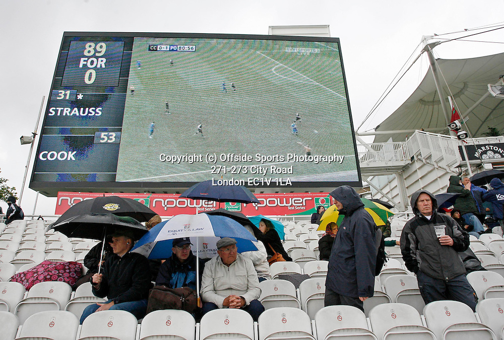 17/05/2008. England v New Zealand - First nPower Cricket Test Match. <br /> Spectators at the cricket shelter from the rain under umbrellas as the FA Cup final is shown on the big screen.<br /> Photo: Glyn Thomas/Offside