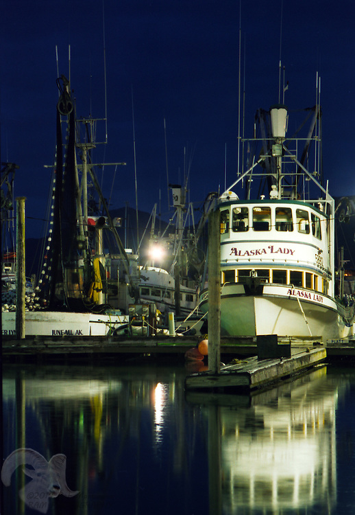 The fishing vessel Alaska Lady moored in the Cordova, Alaska harbor at midnight in July. The vessel is a purse-seiner, a type of fishing that surrounds salmon with a net pulled by another vessel (the skiff) to pull the other end and encircle schools of salmon, as the larger vessel lays the gear around the school. The bottom of the purse-seine net is then pulled together with a purse-like string that closes the bottom, trapping the salmon.