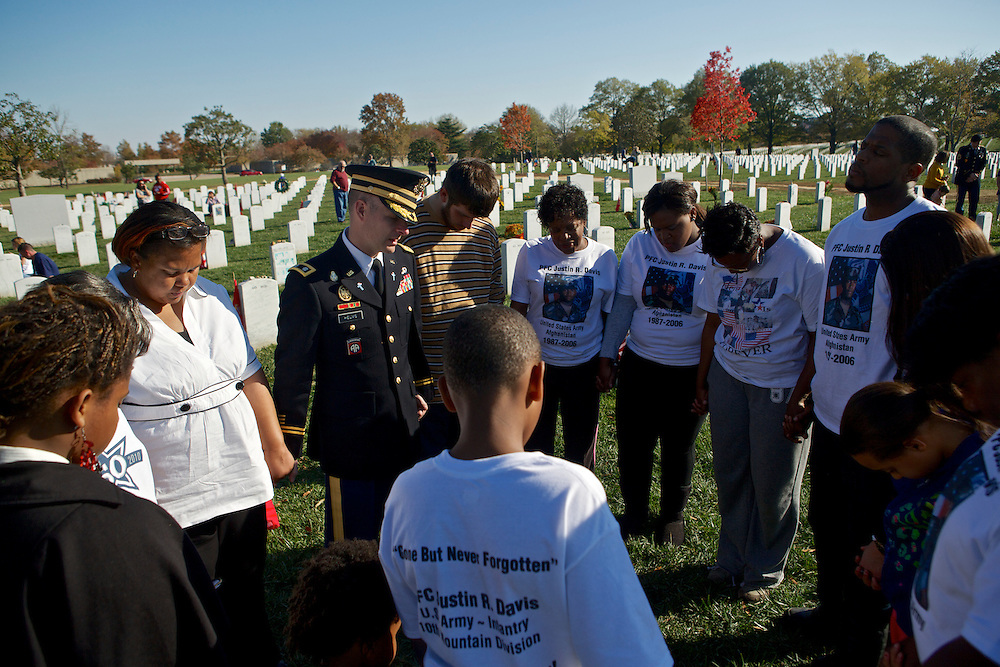 ARLINGTON, VA - NOVEMBER 11: Lt. Col. Thomas Helms, the senior Army Chaplain at Arlington National Cemetery, prays with the family of Pfc. Justin Davis, who died in Afghanistan when he was 19 years old on Veteran's Day at Arlington National Cemetery on November 11, 2012 in Arlington, Virginia.