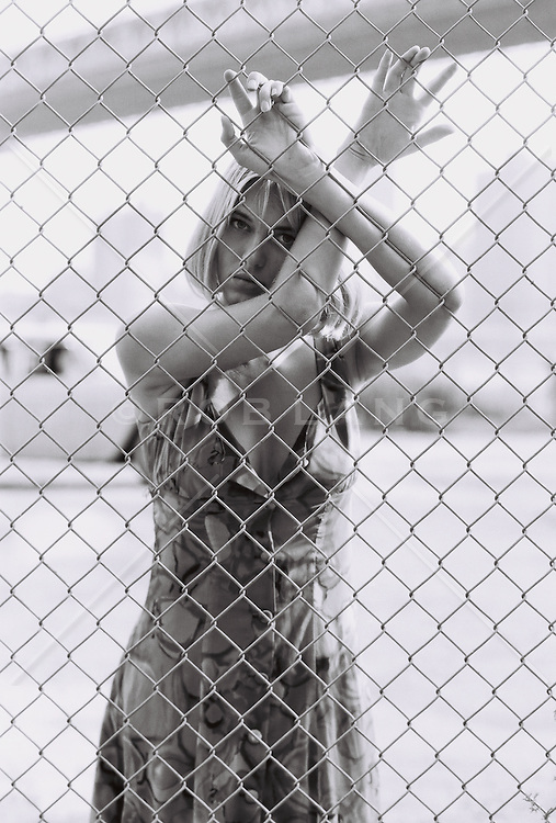 young woman leaning against a chain linked fence in New York