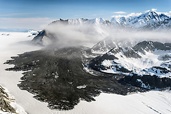 A 4,000-foot-high mountainside released approximately 120 million metric tons of rock in 60 seconds during a landslide onto the Lamplugh Glacier in Glacier Bay National Park and Preserve. In an interview with the Alaska Dispatch News, geophysicist Colin Stark of Columbia University's Lamont-Doherty Earth Observatory, described the slide as &ldquo;exceptionally large.&rdquo; He compared the massive landslide to roughly 60 million medium SUVs tumbling down a mountainside.<br /> <br /> Mountainsides that were held strong by the heavy ice of glaciers become weak when the glaciers retreat. Erosion along with earthquakes are triggers that can cause the weakened slopes to collapse.<br /> <br /> The slide occurred on the morning of June 28  in a remote area of Glacier Bay National Park in southeast Alaska. It was first observed by Paul Swanstrom, pilot and owner of Haines-based Mountain Flying Service. Swanstrom noticed a huge cloud of dust over the Lamplugh Glacier during a flightseeing tour of Glacier Bay National Park several hours after the slide occurred. Swanstrom estimates the debris field to be 6.5 miles long, and one to two miles in width.<br /> <br /> Even two days later, as this aerial photo of the Lamplugh Glacier landslide shows, a dust cloud remained over the unstable mountainside due to still tumbling rock.