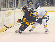 Canisius Griffins'     (#32) tries to clear the puck out of the Griffins zone under the stick of LSSU's Nick MacParland (right) durring the third period of the Griffins 5-4 loss to Lakers Friday night in Sault Ste. Marie, MI.