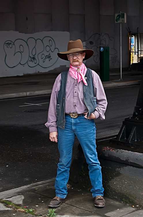 Portrait of a man dressed as a cowboy waiting for a bus.
