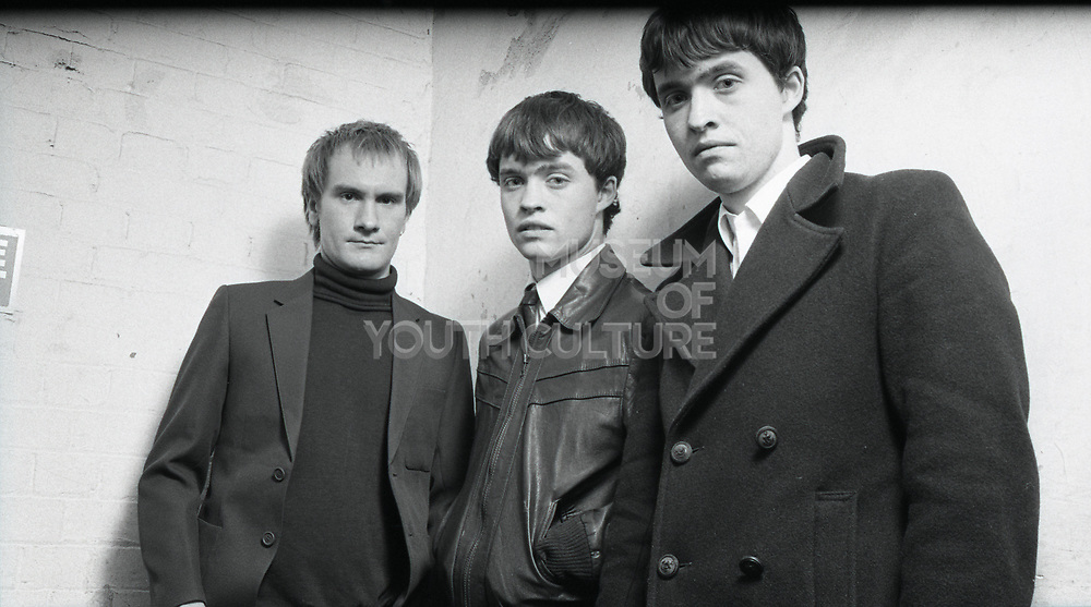 Three members of the band The Bishops standing together looking at camera.
