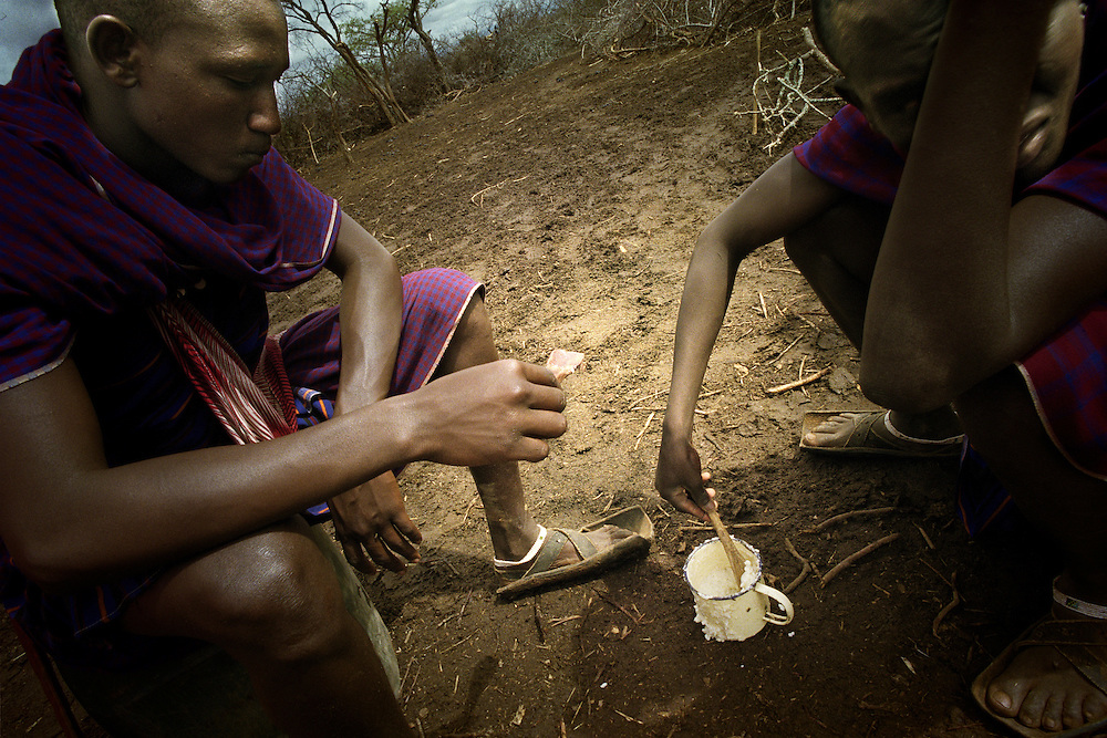 Tanzania, traditional Maasai life. Logolie and Larusai share some maize porridge before setting out again to look after the cattle.