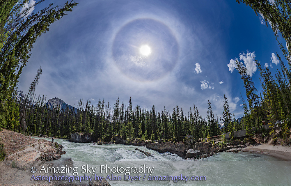 A panorama of a 22&deg; solar halo in the sky over the Natural Bridge and waterfall on the Kicking Horse River in Yoho National Park, BC, June 6, 2016. The day was quite hot but this shows that you can get haloes even on a hot summer day, as the ice crystal clouds causing the halo are high up and cold! <br /> <br /> This is a 7-section panorama taken with the 15mm full-frame fish-eye lens mounted in portrait mode, and moved horizontally to sweep the scene. Stitched with PTGui.