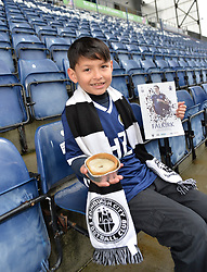 Pictured: 9 year old Joshua Holt before the match at the Falkirk Stadium <br /> <br /> How many Scottish football fans promise themselves a trip to every senior football ground in the country sometime in their life? Probably the majority when they retire.  One such fan who decided to get that milestone ticked off early in his life is nine year old Joshua Holt, from Edinburgh and an Edinburgh City fan, who completed his tour on Saturday 30 December at the Falkirk Stadium when Queen of the South are the visitors.  It has taken four years for Joshua, accompanied by his father Kenny, to complete the tour which started off on 31 August 2013 at Ibrox when Rangers took on East Fife.  A goal feast was on offer that day as Rangers won 5-0 but Joshua, like most five year olds, was more interested in everything else that accompanies a trip to one of the biggest stadiums in the UK.  His father, however, noticed a lot more than the football on the pitch; he had discovered what his football had been missing – a like minded companion.  This was their 'thing' to do together; father and son; come rain or shine.  Not the 'quality time' so often quoted as an essential for a parent but real time doing something they both enjoy.  A shared experience can build stronger bonds than any amount of treats from father to son.  They have travelled over five and a half thousand miles on their long journey and have enjoyed an average 2.9 goals per game.  Not a bad return for the commitment they have shown.<br /> <br /> Fans on match days have their own rituals, be it their lucky scarf; same bus for away games; or heading to the same seat for home games.  Joshua and Kenny go for the four Ps; popcorn, pin badge, programme and pie.  Popcorn for the trip to the ground with the programme and pin badges bought from the club shop as a reminder of the visit.  The catering is always tested especially on these cold days.  For the record Joshua can't see past a Dunfermline pie but his dad prefers a Ross County haggis p