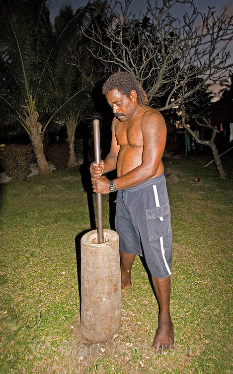 An indigenous Fijian man crushing kava (yangonna) roots to prepare a traditional drink.