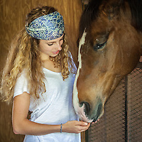 A beautiful young woman lovingly comunicates with her  horse   She is wearing a scarf in her hair, jeans and and a white tee shirt.