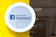 """""""Find us on Facebook"""" round sign hanging inside front window of store on 5th Avenue, Manhattan, NY, February 28, 2010. Sign focus reflects being seen through window with street building reflections on it."""