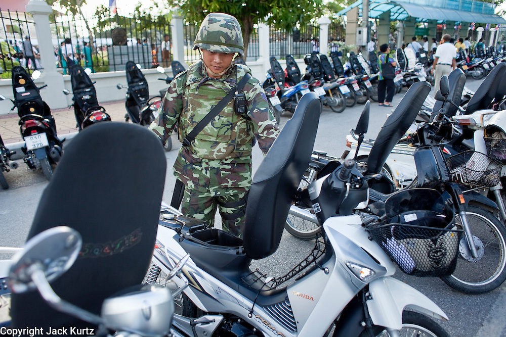 "Sept. 26, 2009 -- PATTANI, THAILAND:  A Thai soldier checks motorcycles for bombs before the Tak Bat Sankatan in Pattani Saturday. People in the insurgency wracked southern provinces are supposed to leave their motorcycles parked with the seats up so authorities can check them for bombs. Buddhists in Thailand's three southern most provinces gathered in Pattani Saturday, Sept 26 to celebrate Tak Bat Sankatan, the day Lord Buddha returned to earth and was greeted by a crawd of his disciples and Buddhist believers who were waiting to offer him food. Buddhists monks representing the 266 ""Wats"" (temples) in the three provinces (Pattani, Narathiwat and Yala) processed through the crowd and were presented with food and gifts.   Photo by Jack Kurtz"