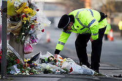 © Licensed to London News Pictures. 06/01/2012. Salford, UK. Flowers and messages have been left at the scene of Anuj Bidve's murder. Police guard the scene and light candles ahead of the visit of Anuj Bidve's parents. Photo credit : Joel Goodman/LNP
