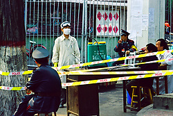China, Taiyuan, 2008. Medical technicians and police monitor the entrance to one of the campuses of Taiyuan Teacher's College during the SARS outbreak in 2003. Students were locked down inside their schools with no notice.