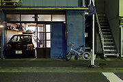 residential housing at night with car and bicycle Japan