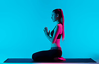 one caucasian woman exercising Vajrasana yoga exercices  in silhouette studio isolated on blue background
