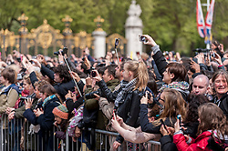 © Licensed to London News Pictures. 02/05/2015. London, UK. People in the crowd take a photo, as in keeping with tradition, the royal birth announcement of the Duke and Duchess of Cambridge's second child, a daughter, born at 8.34am, today, 2 May 2015, is posted on an easel outside Buckingham Palace.  The document is signed by the the delivery team at St Mary's Hospital in Paddington - led by Alan Farthing, the royal surgeon-gynaecologist . Photo credit : Stephen Chung/LNP