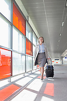 Full length of young businesswoman with luggage walking in railroad station