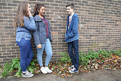 Teenage girls talking to teenage boy  leaning on wall