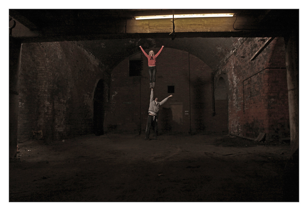 Two cheerleaders doing a single based cupie in the dark arches underneath the train line in Leeds city centre.
