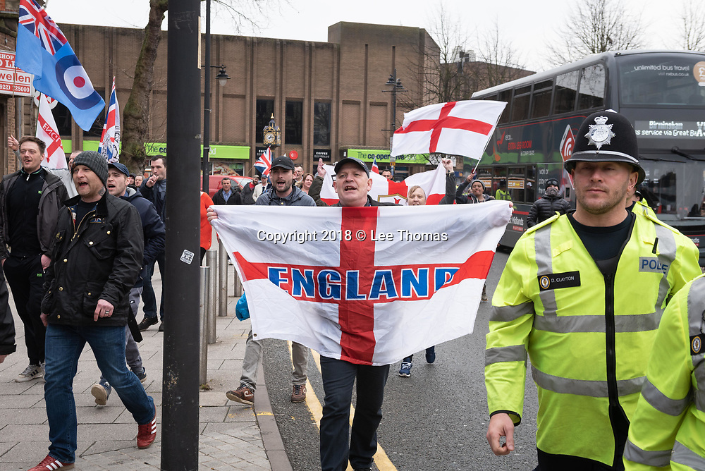 Walsall, West Midlands, UK. 7th April 2018. Pictured: EDL supporters march to their muster point to begin their rally.  / Up to 60 English Defence League supporters take to the streets of Walsall to protest against their claims that the West Midlands town has problems with child exploitation and no-go areas. Scores of police formed a barrier between English Defence League supporters and a vocal anti-fascist contingent, individual protests of which took place only yards away from each other. // Lee Thomas, Tel. 07784142973. Email: leepthomas@gmail.com  www.leept.co.uk (0000635435)