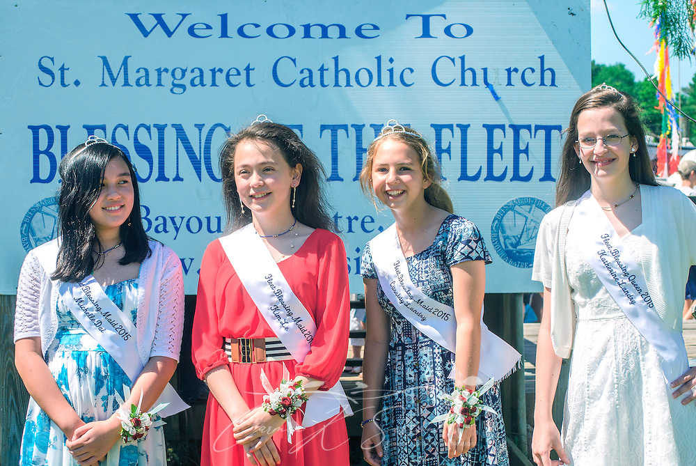 Members of the 66th annual Blessing of the Fleet court wait for Archbishop Thomas J. Rodi (not pictured) to deliver the prayer in Bayou La Batre, Alabama, May 3, 2015. From left are Fleet Blessing Maid Michelle Dai, Fleet Blessing Maid Kim Le, Fleet Blessing Maid Cassidy Landry, and Fleet Blessing Queen Katherine Landry. The first fleet blessing was held by St. Margaret's Catholic Church in 1949, carrying on a long European tradition of asking God's favor for a bountiful seafood harvest and protection from the perils of the sea. The highlight of the event is a blessing of the boats by the local Catholic archbishop and the tossing of a ceremonial wreath in memory of those who have lost their lives at sea. The event also includes a land parade and a parade of decorated boats that slowly cruise through the bayou. (Photo by Carmen K. Sisson/Cloudybright)