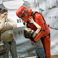 "Eight year old Connor Lindau , who has autism, hugs Adam Canon, dressed as a Magma Trooper from Star Wars as his mother, Crystal Landau (left) watches in excitement in the background during the first day of the Tree City Comic Con in Boise, Idaho. ""He (Connor) is just in heaven being here. Star Wars and My Little Pony are two of his favorite things in life"", said Crystal. Adam, who's son was diagnosed with a mild form of autism last year, is part of the Utah branch of the 501st Legion. The 501st Legion is a world wide Star Wars based costuming organization. The Tree City Comic Con continues Saturday from 10am until 8pm at Expo Idaho. Friday October 17, 2014"
