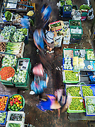 "21 DECEMBER 2015 - BANGKOK, THAILAND:  People walk through the produce section of Pak Khlong Talat, also called the Flower Market. The market has been a Bangkok landmark for more than 50 years and is the largest wholesale flower market in Bangkok. A recent renovation resulted in many stalls being closed to make room for chain restaurants to attract tourists. Now Bangkok city officials are threatening to evict sidewalk vendors who line the outside of the market. Evicting the sidewalk vendors is a part of a citywide effort to ""clean up"" Bangkok.      PHOTO BY JACK KURTZ"