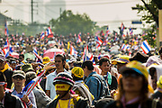 """09 DECEMBER 2013 - BANGKOK, THAILAND: Thai anti-government protestors gather on the sidewalk in front of Government House in Bangkok. Thai Prime Minister Yingluck Shinawatra announced she would dissolve the lower house of the Parliament and call new elections in the face of ongoing anti-government protests in Bangkok. Hundreds of thousands of people flocked to Government House, the office of the Prime Minister, Monday to celebrate the collapse of the government after Yingluck made her announcement. Former Deputy Prime Minister Suthep Thaugsuban, the organizer of the protests, said the protests would continue until the """"Thaksin influence is uprooted from Thailand."""" There were no reports of violence in the protests Monday.      PHOTO BY JACK KURTZ"""