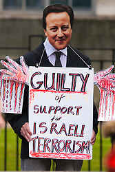 London, August 23rd, 2014. A demonstrator wears a David Cameron mask and proclaims his guilt for supporting Israel as hundreds of pro- Palestine protesters demonstrate outside Downing Street demanding that Britain stops arming Israel.
